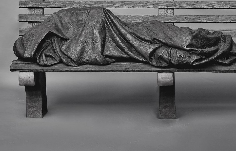 image of a sculpture depicting Jesus as a homeless person lying on a bench